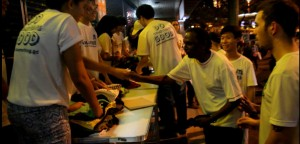 Volunteers giving out t-shirts to the homeless